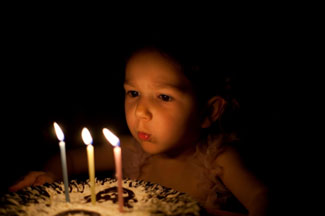 child-blowing-out-candles-325px